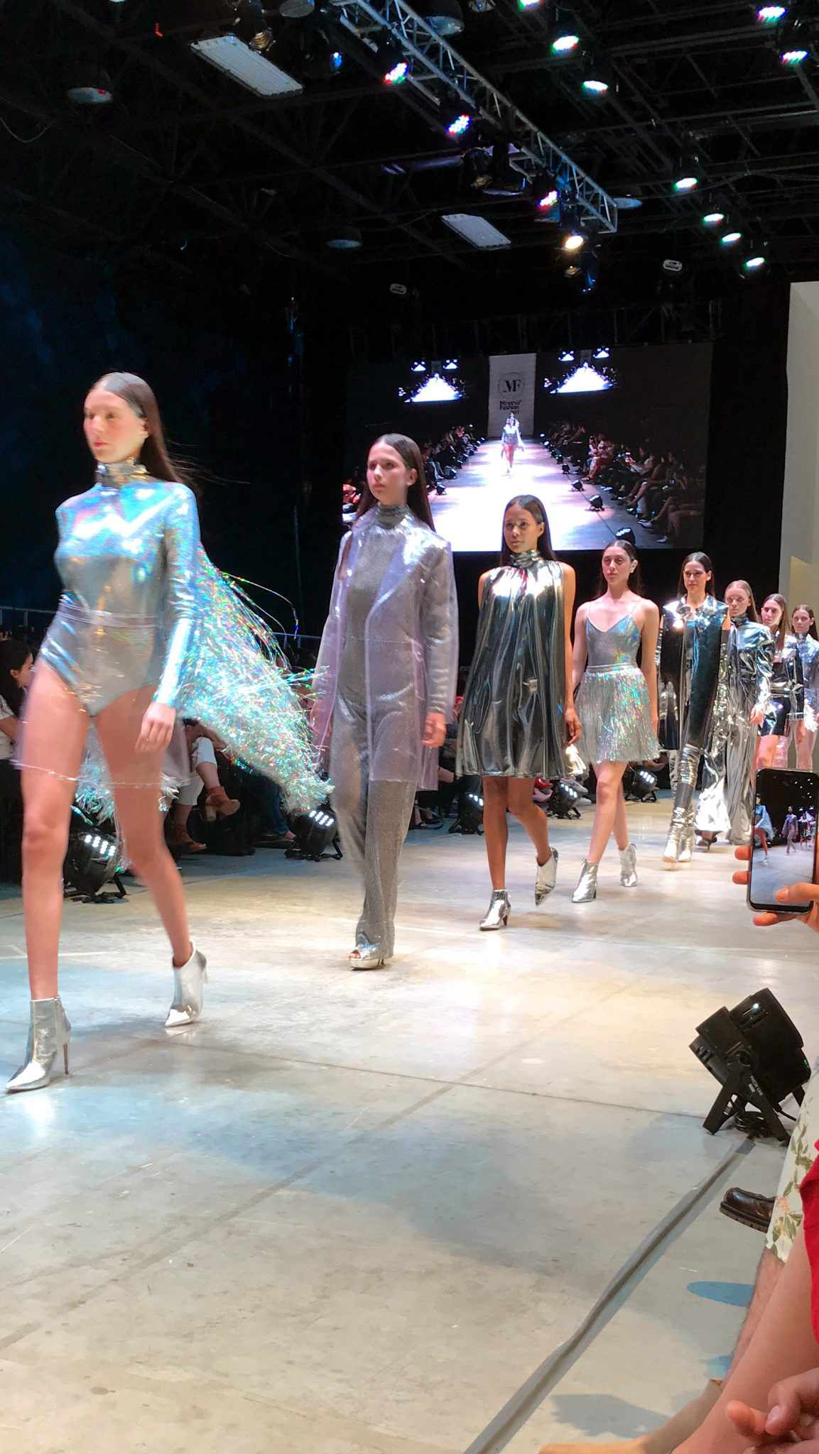 Model on the runway, wearing a silver jacket with tinsel, silver boots