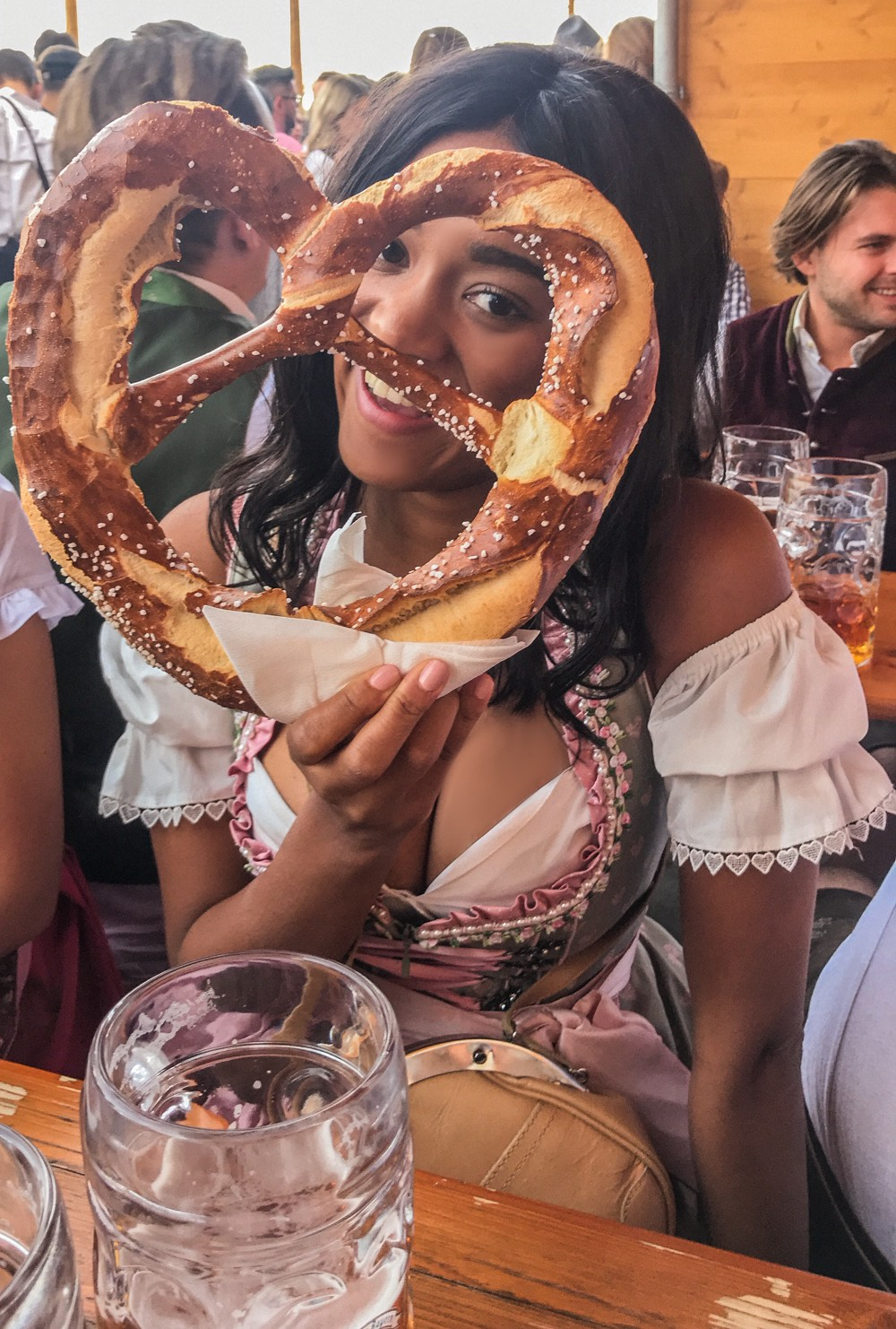 Girl sitting in a Dirndl at the Oktoberfest holding a Prezel