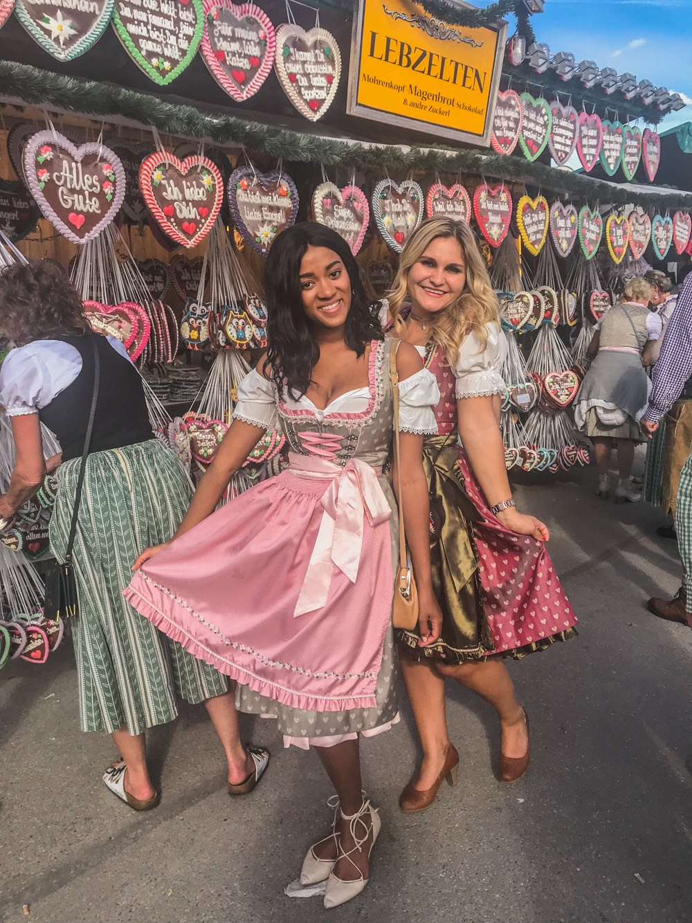 Girl standing in a Dirndl at the Oktoberfest in front of Lebkuchenkerzen