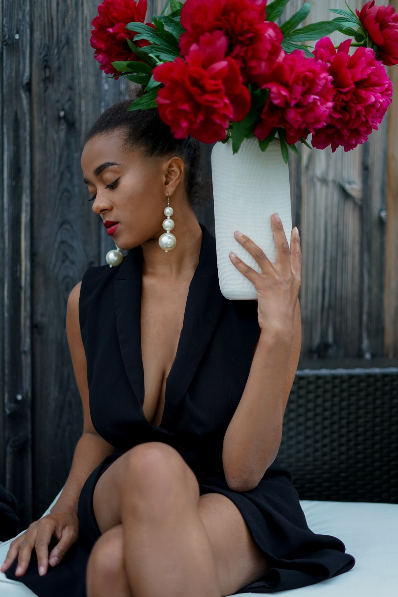 Girl wearing statement earrings and peonies