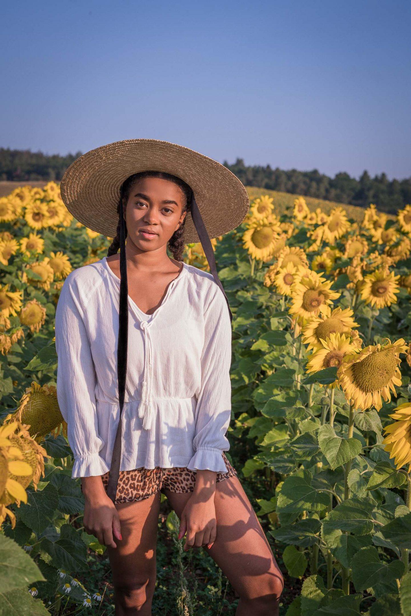 Black Fashion Blogger in a Sunflower Field best summer hats to wear in 2020