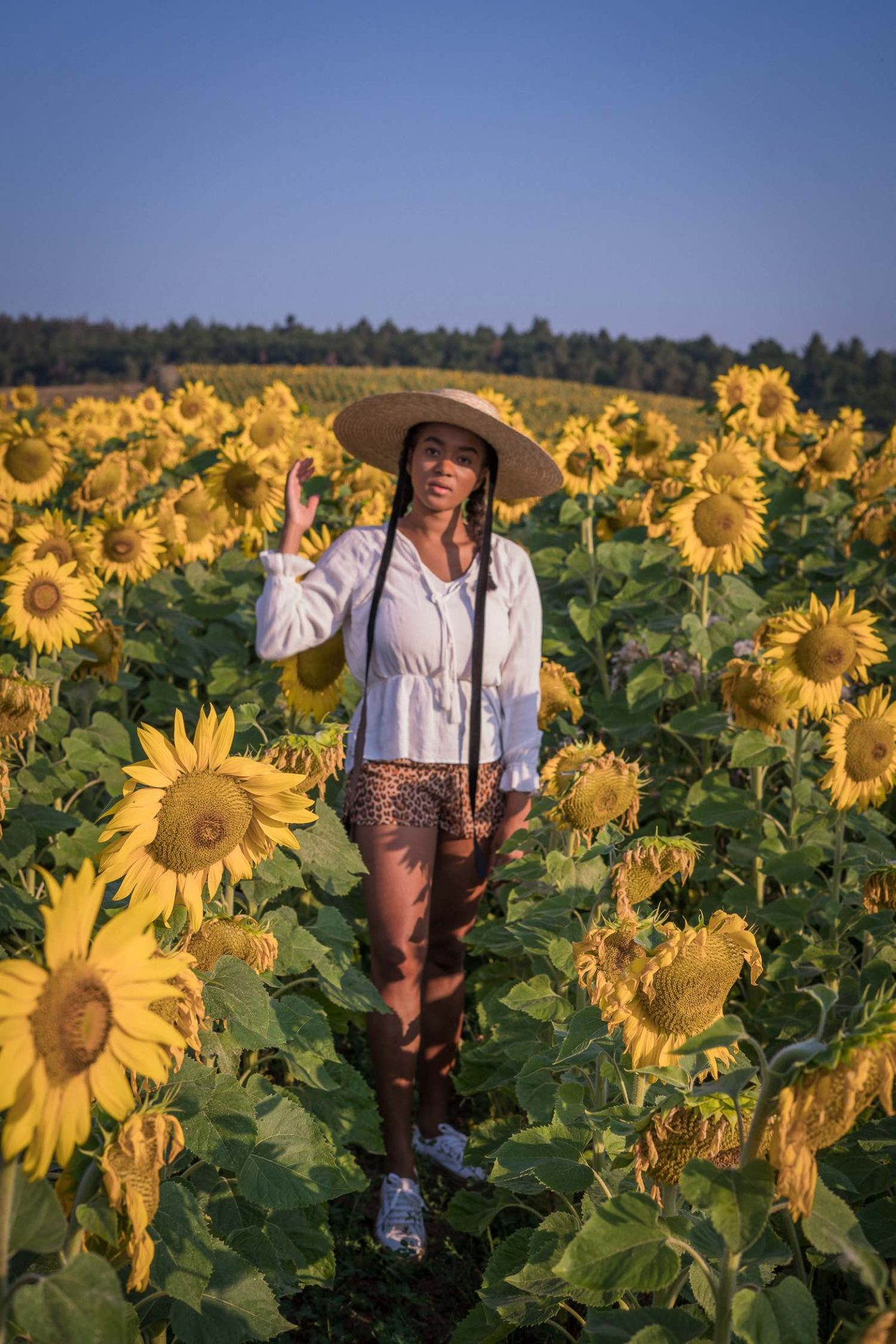 Black Fashion Blogger in a Sunflower Field wearing summer hats