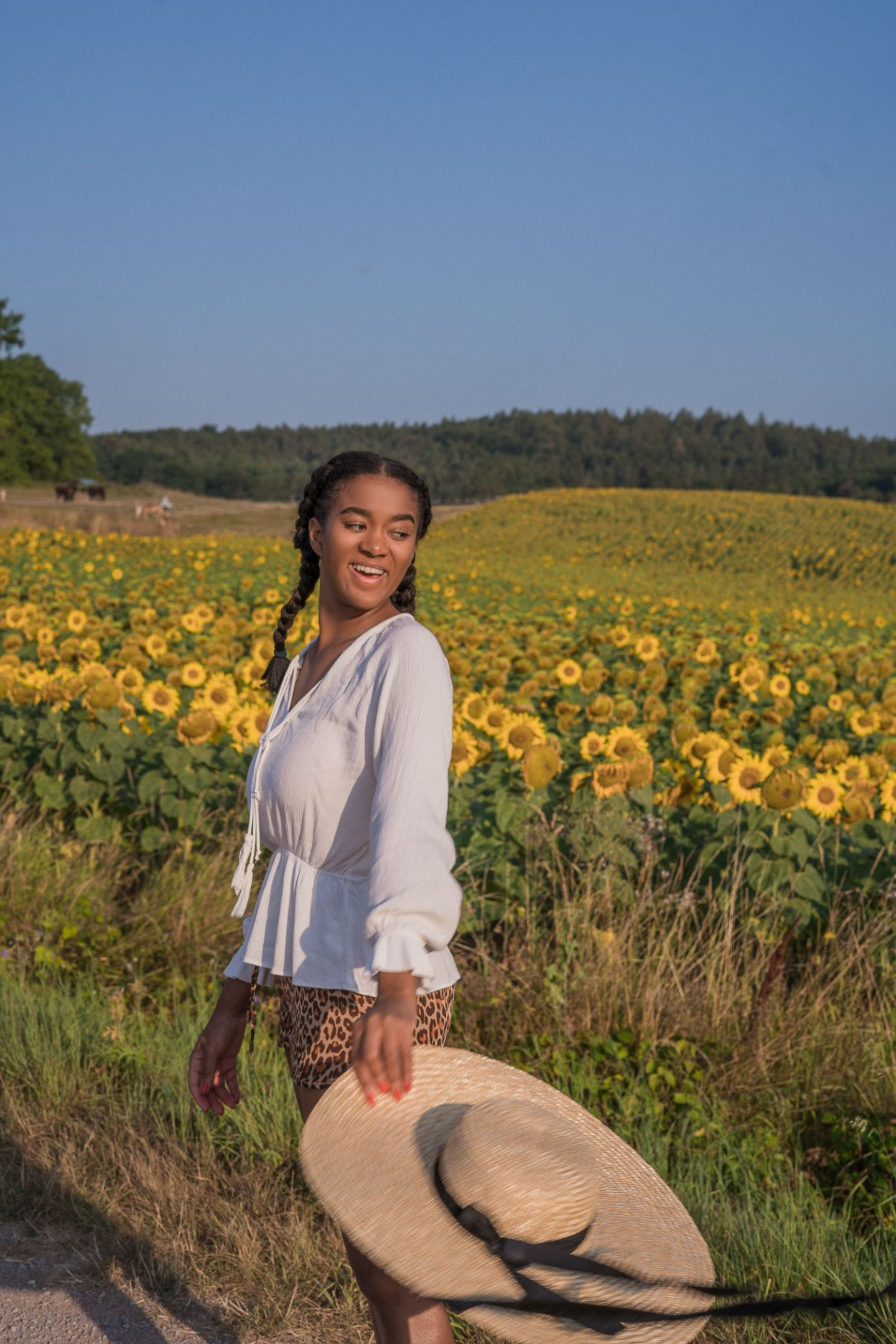 Black Fashion Blogger in a Sunflower Field wearing a hat in summer